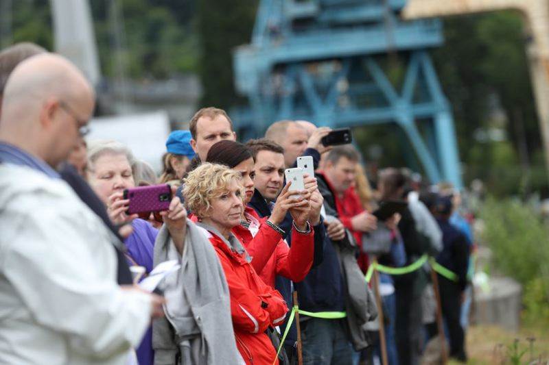 PAMPLIN MEDIA GROUP: JAIME VALDEZ - Portlanders waited up to three hours for the launch in a VIP area cordoned off inside Zidell Marine, and others outside the fence on the greenway beside the river.