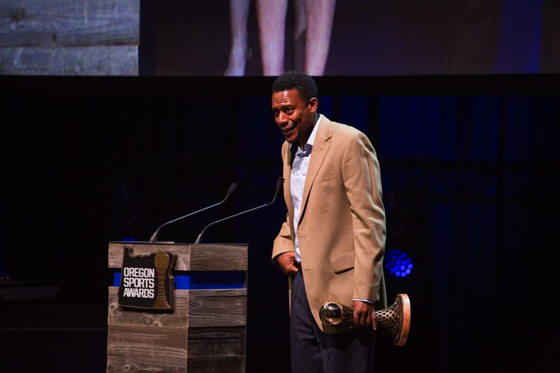 TRIBUNE PHOTO: ADAM WICKHAM - Oregon Ducks coach Robert Johnson accepts George Pasero Team of the Year awards for women's indoor and outdoor track and field and cross country.