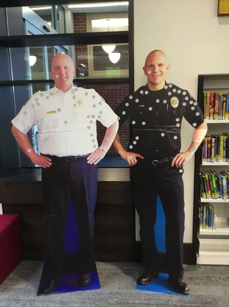 PHOTOS COURTESY: CITY OF OC - Clackamas Fire Chief Fred Charlton and Oregon City Police Chief Jim Band have become celebrity cutouts for kids to vote on using stickers at the Oregon City Public Library.