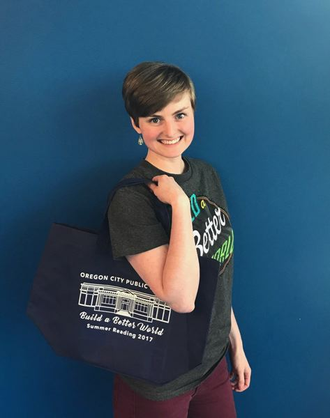 PHOTOS COURTESY: CITY OF OC - When you sign up for Oregon City's Adult Summer Reading program, you receive this tote bag (while supplies last), modeled by library assistant Hannah Bostrom.
