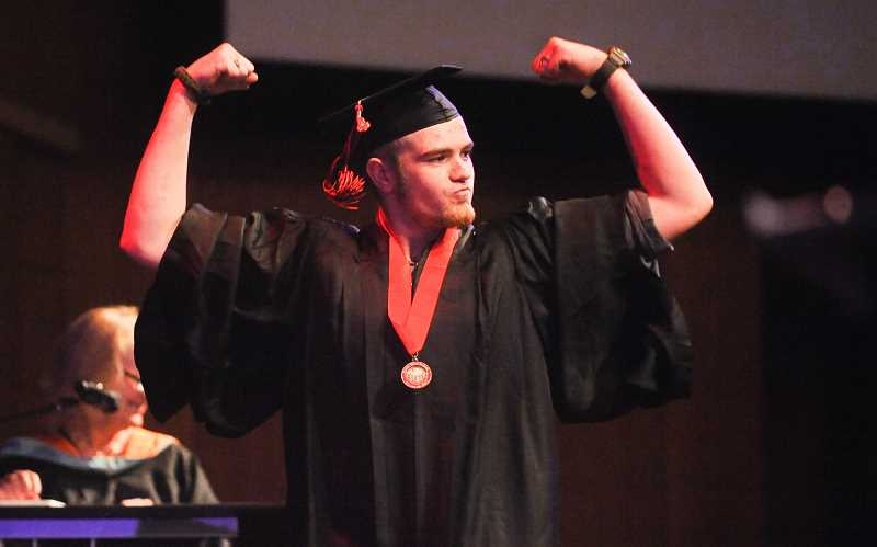 POST PHOTO: JOSH KULLA - Sandy High School graduate Cordell Pyle flexes for the crowd Friday at the schools 2017 commencement exercise at Rolling Hills Church in Tualatin.