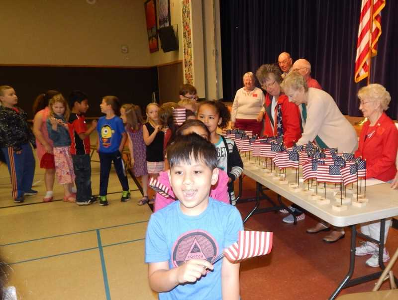 BARBARA SHERMAN - On June 14 in the Durham Elementary cafeteria, King City Lions Club members hand out American flags to all the first-graders, a decades-long tradition that starts with the young scholars studying the American flag and learning patriotic songs ahead of the event.