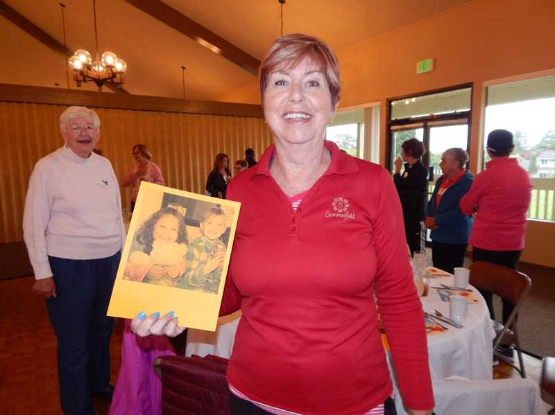 BARBARA SHERMAN - Sandy Brewer, chair of the Summerfield Women's Golf Club's annual charity fundraiser, holds a photo of children who have benefitted from staying at the Good Neighbor Center for homeless families. The photo of Brewer was taken after the club's Member-Guest Golf Tournament played partially in the rain on June 15 as members, including Marilyn Katz (left), and guests gathered before lunch.