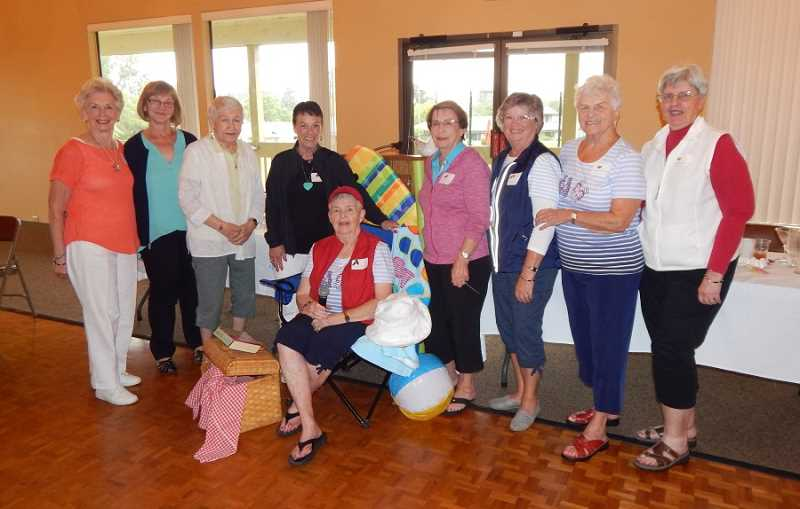 BARBARA SHERMAN - Summerfield Women's Golf Club's Member-Guest Luncheon chair Wendy Pfeifer sits in a beach chair surrounded by her committee members (from left) Astrup, J. Knutson, Tyler, McPherson, Primrose, C. Smith, Montgomery and Launder.