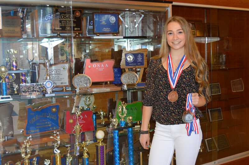 CINDY FAMA - Madalyn Spitzer in front of the CHS trophy case with just some of the medals she's won in gymnastic competitions while representing Colton High School. But it wasn't until graduation time that the school changed its policy towards club sports and presented her with a varsity letter, with four bars.
