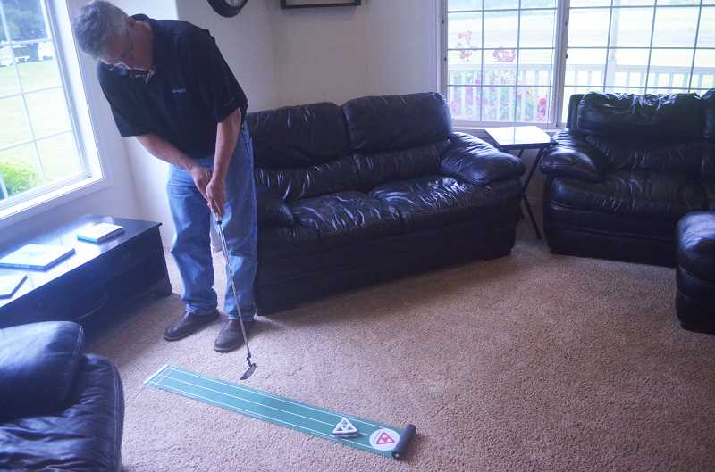 SPOKESMAN PHOTO: COREY BUCHANAN - Dave Grill putts the delta putt toward the target at his home in Wilsonville.