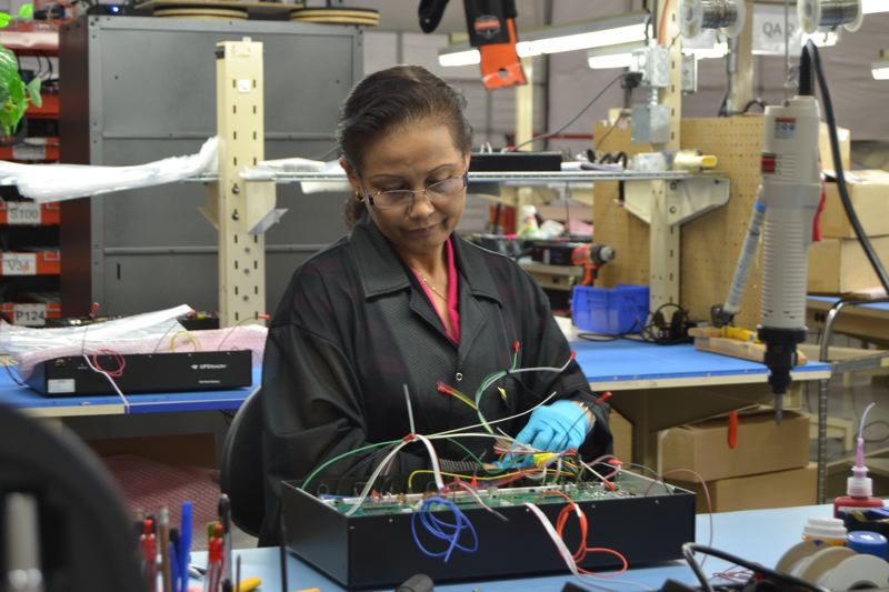 PAMPLIN MEDIA GROUP: JULES ROGERS - While some labor is outsourced to China, much is locally sourced near the Wilsonville headquarters. Electricians detail batteries in the warehouse at the back of the office.