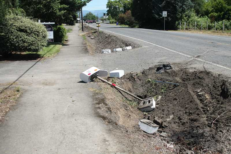 PIONEER PHOTO: CONNER WILLIAMS - A mailbox can be seed uprooted from the ground after a two-car crash near the intersection of Highway 211 and Leroy Street in Molalla resulted in three people transported for injuries along with a dog around 12:30 p.m. Wednesday, June 21.