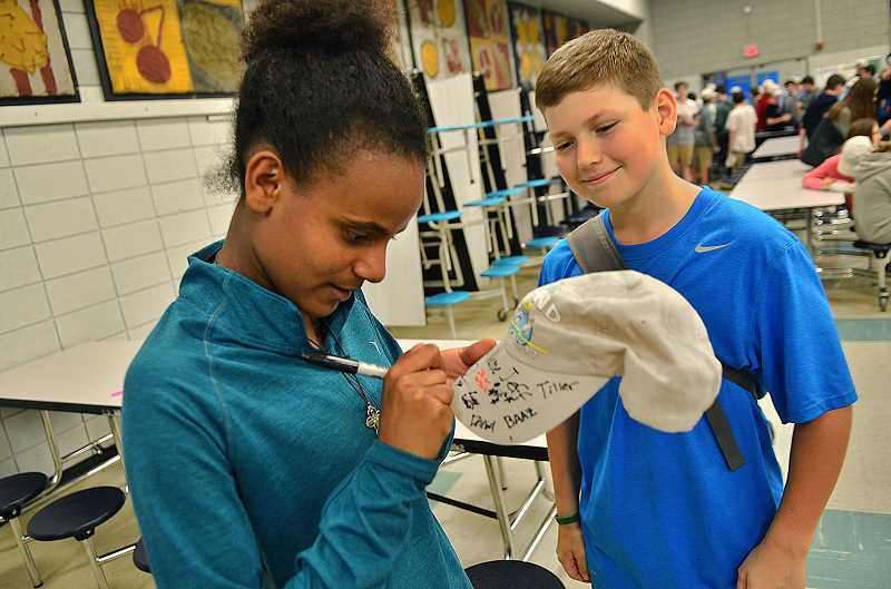 REVIEW PHOTO: VERN UYETAKE - Sadie Fashana signs her John Hancock on Cody Taylor's cap at last week's eighth-grade celebration at Lakeridge Junior High.