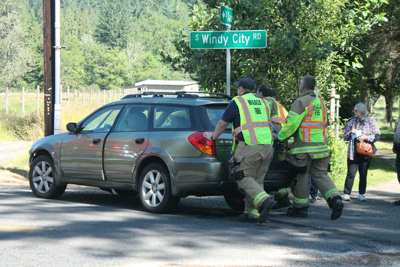 PIONEER PHOTO: CONNER WILLIAMS - Officials from the Molalla Fire District push the Subaru Outback off of Windy City Road in Mulino after it collided with a Chevrolet Tahoe while attempting to turn onto the road from Salo Road around 10 a.m. on Thursday, June 22.