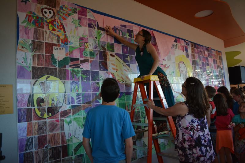 SPOTLIGHT PHOTO: COURTNEY VAUGHN - Veronica Reeves and Jennifer Hanson, both artists in residence working with Otto Petersen Elementary School, help tear down butcher paper that was covering the mosaic prior to the unveiling this week. Reeves and Hanson worked with students and staff for months to design, create and install the project.
