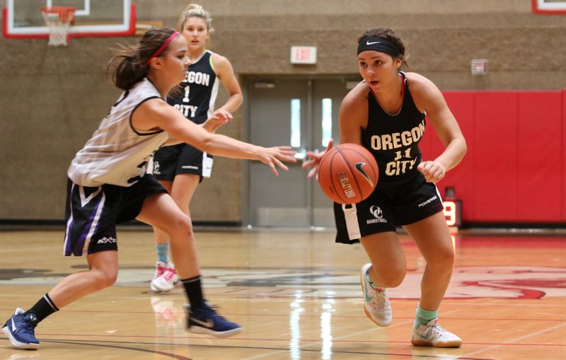 REVIEW/NEWS PHOTO: JIM BESEDA - Oregon City's Tyra Bradford (11) manuevers around South Eugene's Madison Elmore during Friday's opening round of the End Of The Trail River City Classic girls' basketball tournament at Oregon City High School.
