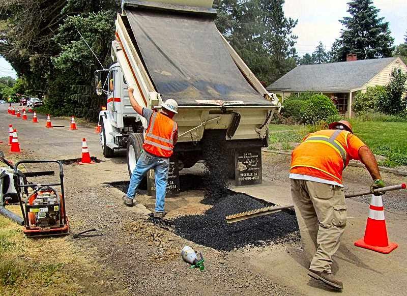 ERIC NORBERG - A crew from Just Bucket Excavating of Albany, which contracts with PDOT to repair potholes in Southeast Portland, starts filling a very large rectangular pothole on S.E. 37th between Insley and Steele, on the afternoon of June 7.