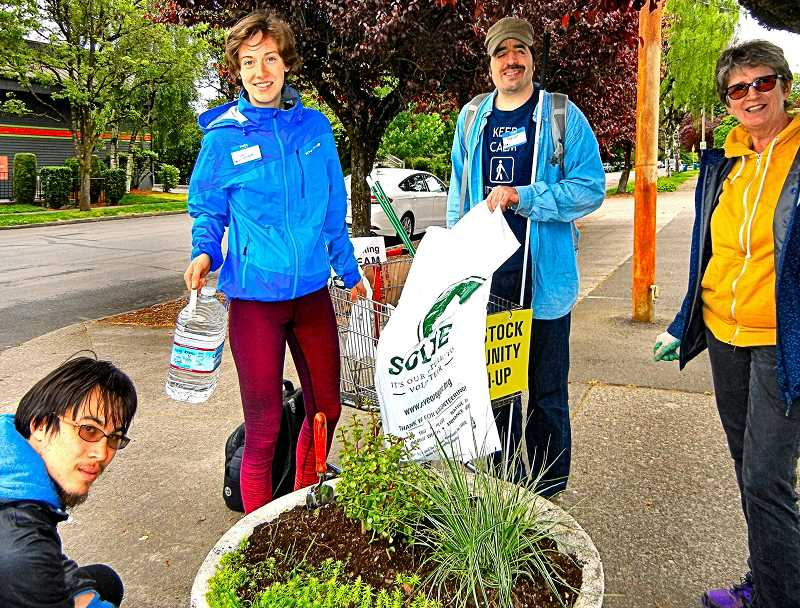 ELIZABETH USSHER GROFF - Re-planting a flowerpot in front of Woodstock Wine & Deli, during the Woodstock Boulevard annual community cleanup are, from left: Jonathan Straus, Jordyn, Trevor Attenberg, and Ingrid Mather.