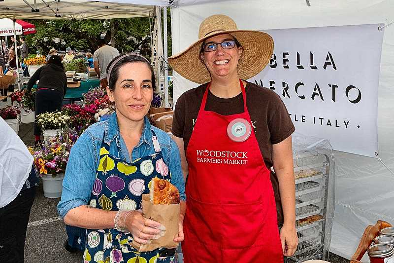 """DAVID F. ASHTON - New bakery owner Michelle Vernier from """"Bella Mercado"""" spends a moment with Woodstock Farmers Market Manager Emily Murnen."""
