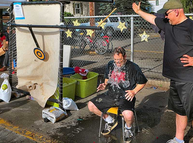 DAVID F. ASHTON - Students delight in repeatedly soaking Llewellyn Principal Joe Galati at the pitching booth of this years early-June Llewellyn Carnival.