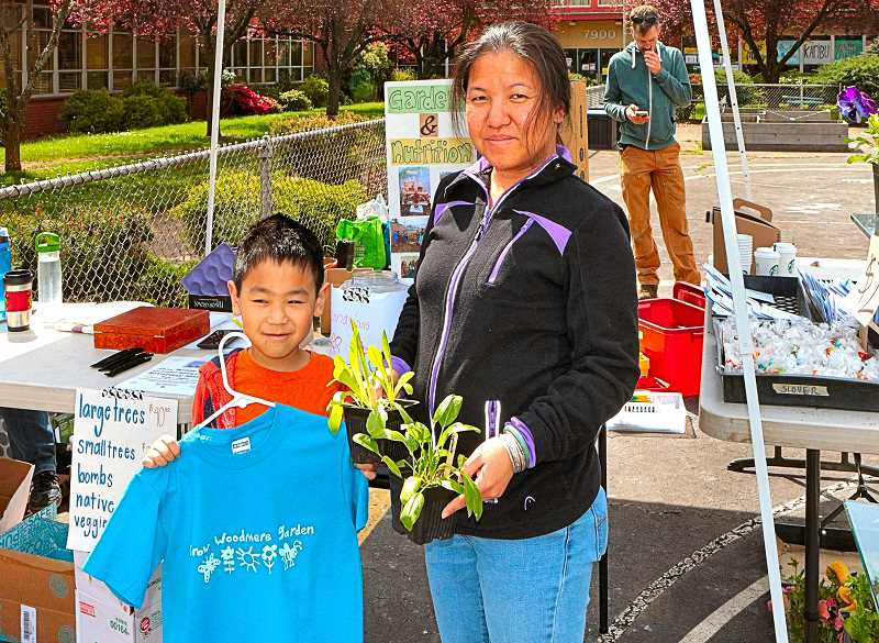 DAVID F. ASHTON - Ngoc Nguyen, with Aland Dinh, show their purchases at the Woodmere Multicultural Education fundraising Garden Plant Sale.