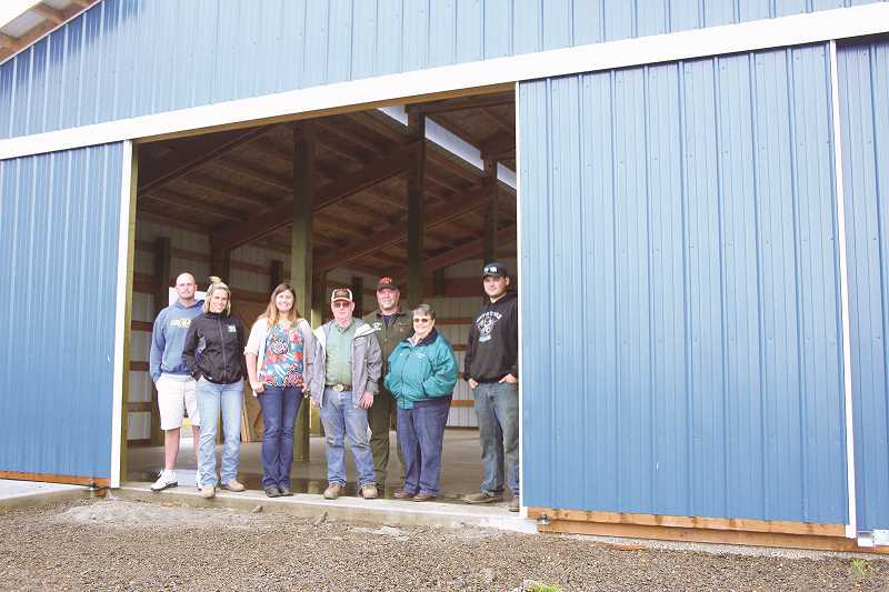 PHIL HAWKINS - Members of the Friends of Gervais FFA and Gervais High School staff members gather at the entrance of the barn they helped raise the money to construct through the program's annual banquet.