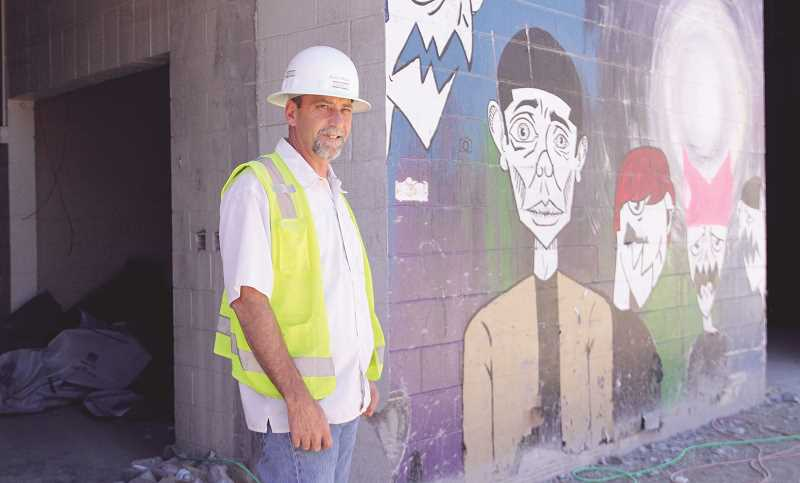 INDEPENDENT PHOTO: LINDSAY KEEFER - John O. Henri stands beside a mural at Woodburn High School that was recently uncovered after demolition and construction work began to reconstruct the part of the school that fell victim to a fire five years ago. The murals will unfortunately be covered up again, Henri said, but plans are in the works to have new ones painted when the project is finished.