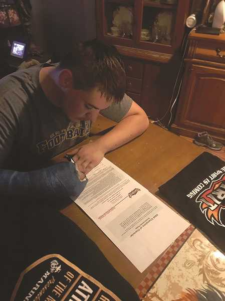 COURTESY OF PETER MCKINLEY - Gervais 2017 graduate Peter McKinley inks his commitment to the newly-formed Ottawa Spirit football program in Arizona.