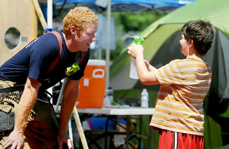 GARY ALLEN - Volunteer Jayson Mcconaghy, 10, helped walkers battle the 100-plus-degree heat Saturday with his trusty spray botttle.