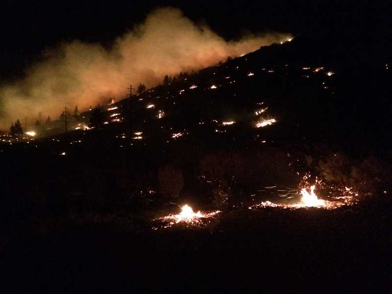 PHOTO BY SUE MATTERS - The Warm Springs fire on Sunday night, with flares from burning juniper trees.