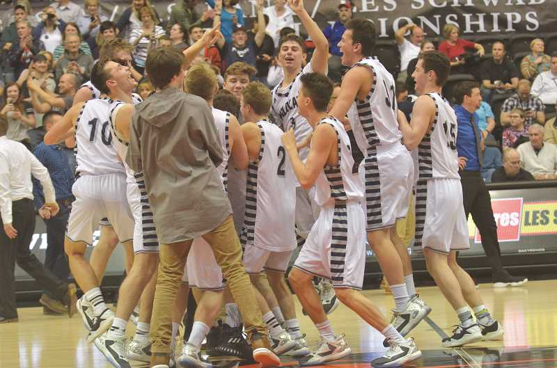 SPOKESMAN FILE PHOTO: COREY BUCHANAN - Wilsonville boys basketball players congregate at center court after capturing their second consecutive state championship at Gill Coliseum in March.