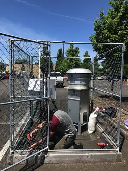 PHOTO COURTESY JESSICA APPLEGATE - A DEQ technician dismantles an air quality monitor installed in a parking lot near Bullseye Glass. DEQ plans to redeploy the monitor to The Dalles.