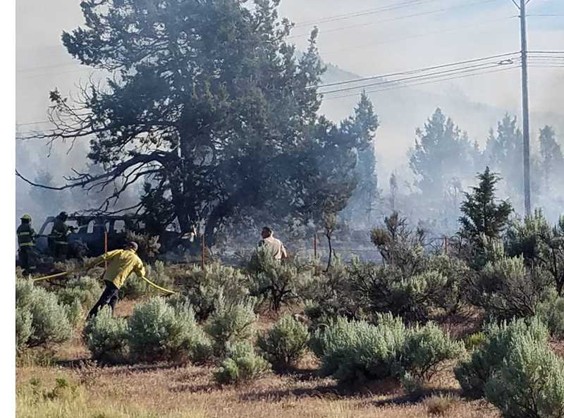 PHOTO BY LINDA LARSON - The burnt shell of the Chevrolet Suburban is visible beside the tree at left, with firefighters trying to stop the spread of the wildfire.