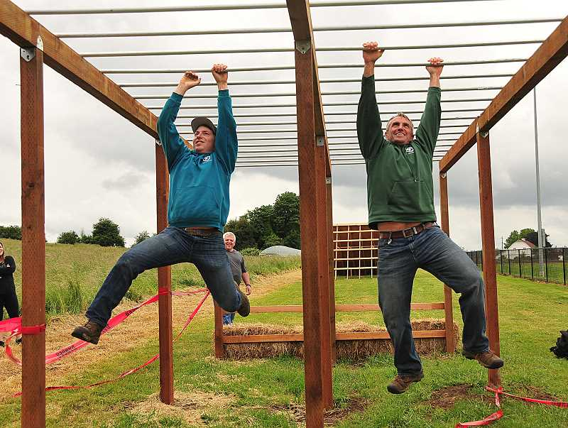 REVIEW PHOTO: VERN UYETAKE - Parks & Rec staffers Kyle Bateman (left) and Eric Hirshberger test out the new monkey bars they designed for the Howl at the Moon 5K Adventure Run, which is scheduled for July 28 at Luscher Farm.