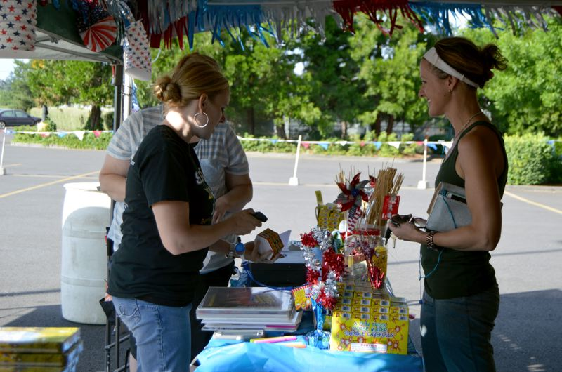 SPOTLIGHT PHOTO: NICOLE THILL - Marisa Brady, right, a former St. Helens resident, checks out at a fireworks stand while being helped by Noelle Freshner, the St. Helens School District band director. Brady, who now lives in California and was visiting her parents in St. Helens for the weekend, said she was excited to light off fireworks with her children. The fireworks sales are an annual fundraiser for the band program.