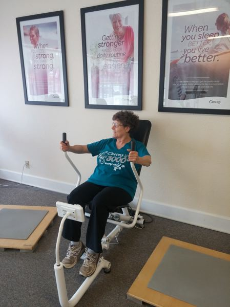SUBMITTED PHOTO - Susan Pape works out on the squat machine at Damascus Curves; the business attracts many members from the Happy Valley and Damascus areas.