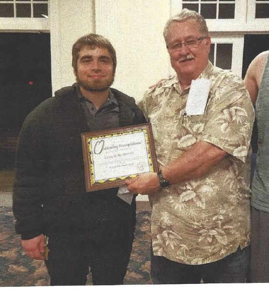 Oregon SenateAires secretery Ken Daniels (right) presents an Award of Excellence from the International Barbarshop Harmony Society to grant writer Craig Holfield, 26.