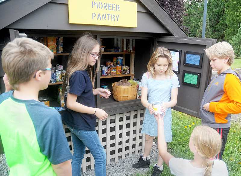 SETH GORDON - From left to right, members of the Ewing Young Elementary School K-Kids program Wyatt Stapleton, Lily Sommers, Jade Gentile (bottom right) and T.J. Primavera, stock the food pantry they created as a club project.