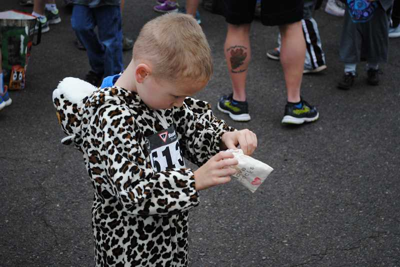 NEWS-TIMES PHOTOS: EMILY GOODYKOONTZ - Jacob Green opens a bag containing a love rock, a little gift received by everyone who completes the Love Rocks Run.