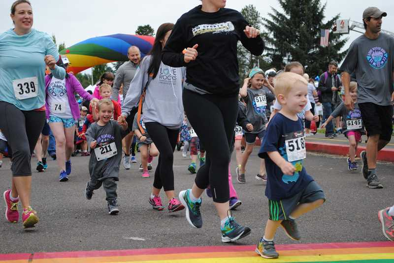 NEWS-TIMES PHOTO: EMILY GOODYKOONTZ - Kids and their parents race towards a mini obstacle course at the start of the kid's fun run.