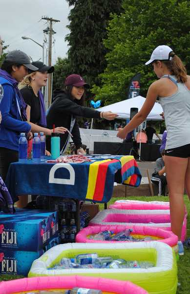 NEWS-TIMES PHOTOS: EMILY GOODYKOONTZ - Ella Olsen (right) gets water and stickers from Tessa Nelson after the race. Nelson is the assistant manager at the local Dutch Bros and provides the runners with cold water.