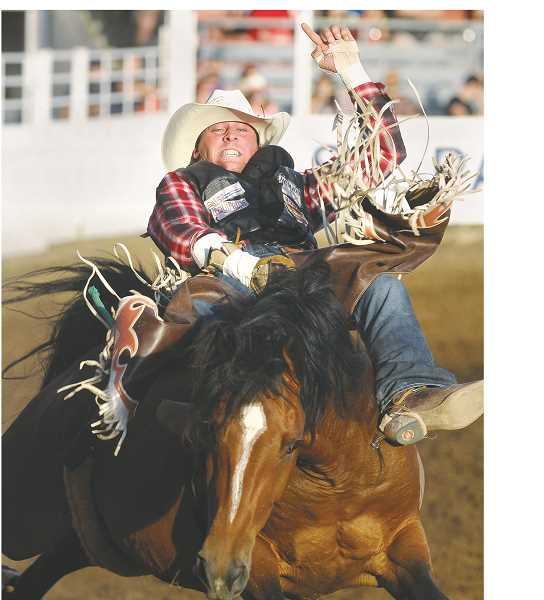 GARY ALLEN - A saddle bronc rider does his best to stay atop the mount for the full eight seconds Friday and earn some of the thousands of dollars in purse money.