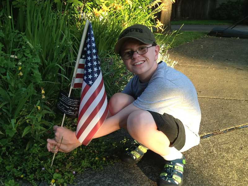 SUBMITTED PHOTO - Boy Scout Harrison Halsted places a flag in a Wilsonville lawn Thursday, June 29.