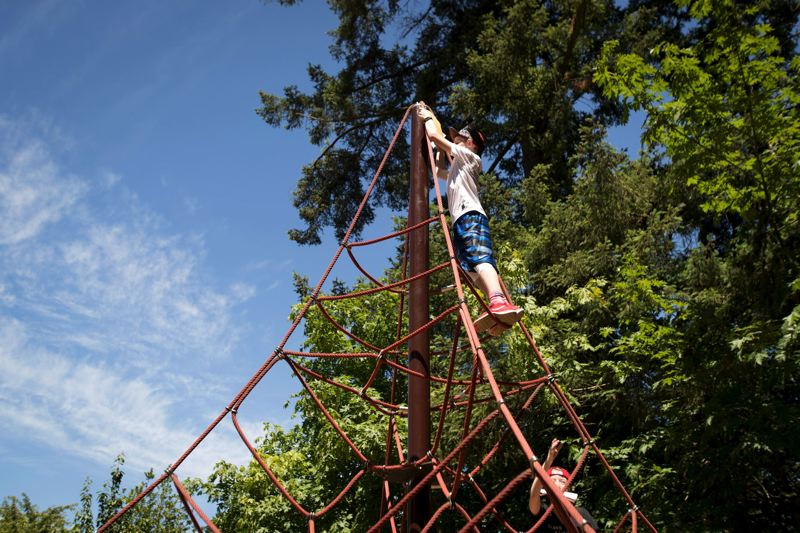 TIMES PHOTO: JAIME VALDEZ - Sawyer Johnson climbs up a climbing apparatus at Tualatin Community Park to find a clue in a scavenger hunt  organized by the Tualatin Public Library.