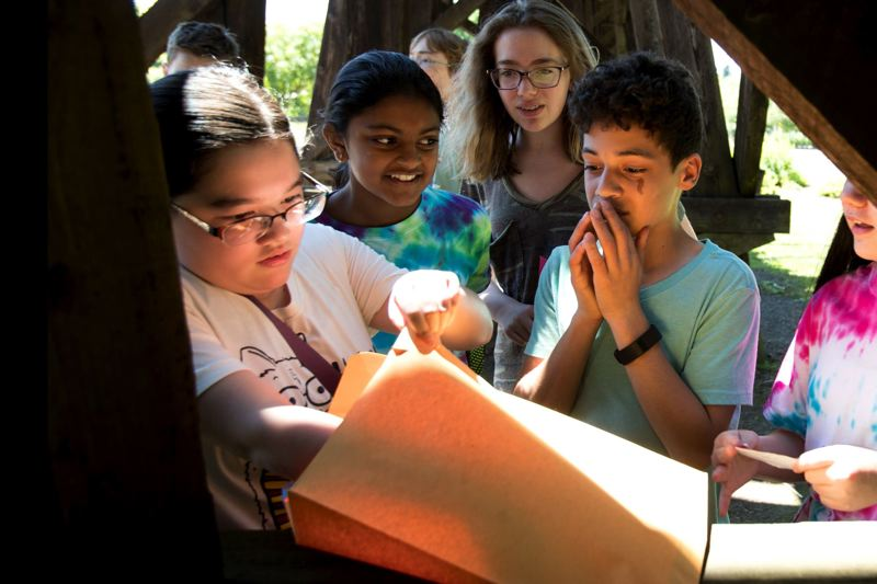 TIMES PHOTO: JAIME VALDEZ - Hannah Rhee, Satvika Vladapu, Faith Rhee and Avery Morris react after finding a clue in a scavenger hunt at Tualatin Community Park organized by the Tualatin Public Library.