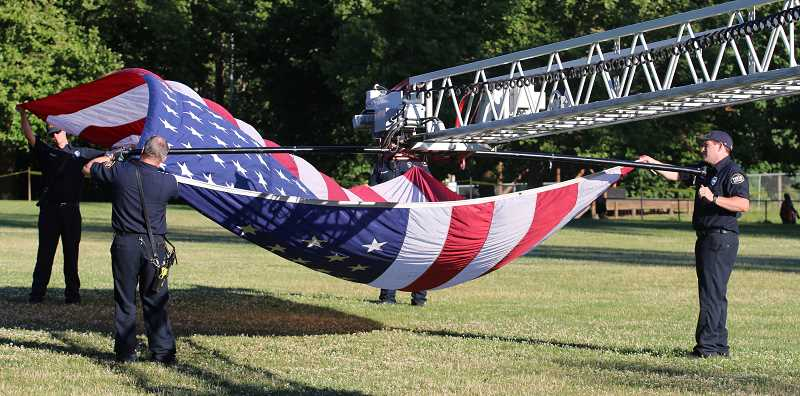 Tualatin Valley Fire and Rescue brought their hook and ladder truck to display a giant American flag for the start of West Linns July Fourth event at Willamette Park.
