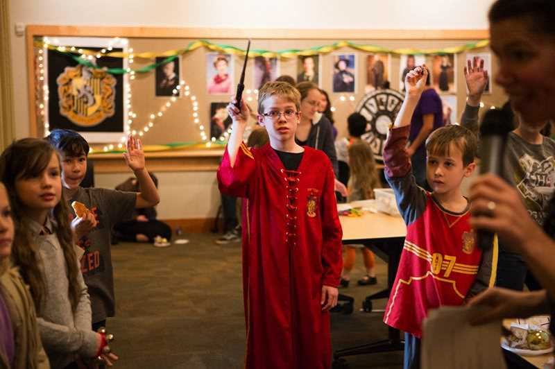 ADAM WICKHAM - Ben Nickle, 11, raises his wand to answer a trivia question about the 'Harry Potter' series in the Tualatin Public Library's community room at the 'Holidays at Hogwarts' party last December.