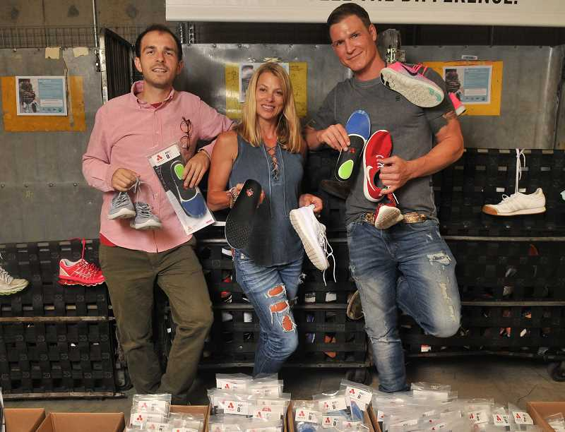 STAFF PHOTOS: VERN UYETAKE  - From left, Protalus employees Ian Romansky, Krista Taylor and owner Chris Buck hold insoles, which will be inserted into new and gently used shoes they are collecting for distribution to Portland Rescue Mission. The public is encouraged to donate shoes for homeless people.