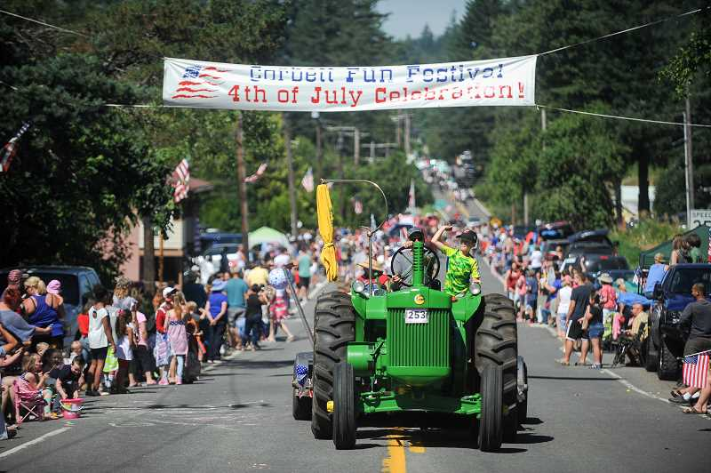 OUTLOOK PHOTO: JOSH KULLA - A tractor makes its way down the Historic Columbia River Highway Tuesday as part of the annual Corbett Fourth of July parade between Springdale and Corbett. Thousands of people lined the roadway for the popular event.