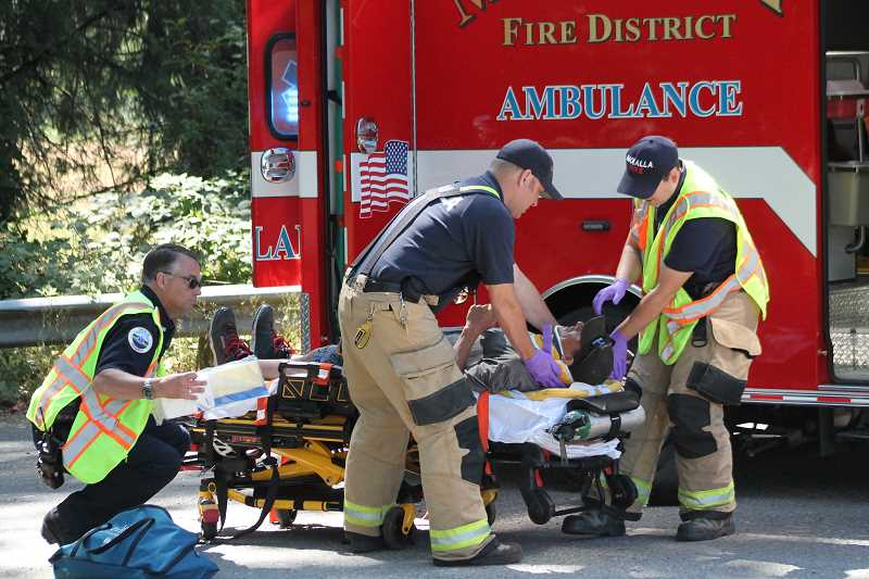 PIONEER PHOTO: CONNER WILLIAMS - Officials from the Molalla Fire District place the unidentified driver of the rear-ended van into a neck brace and stretcher.