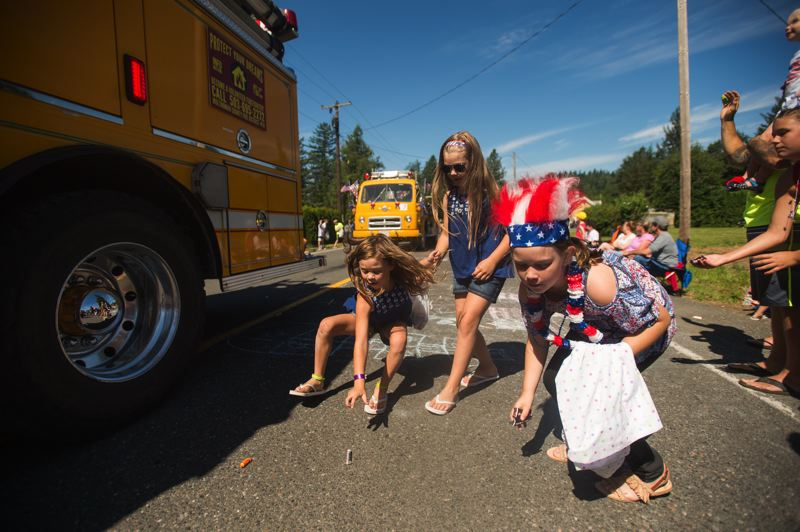 OUTLOOK PHOTO: CLARA HOWELL - Children rush to collect candy thrown from a passing fire engine Tuesday morning during the Corbett Fourth of July Parade.
