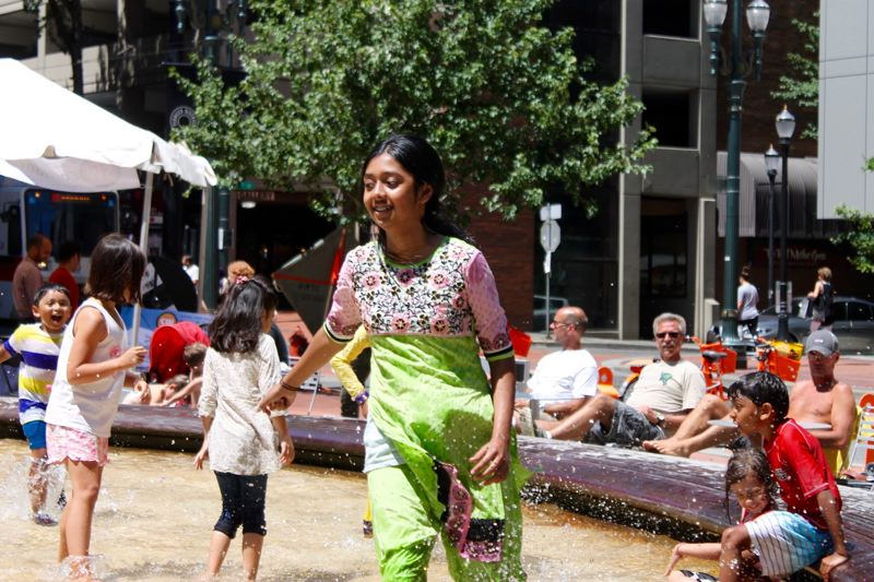 TRIBUNE PHOTO: LYNDSEY HEWITT - Children played in the Teachers Fountain at Director Park on Saturday afternoon, July 8, at the first Portland International Muslim Cultural Festival.