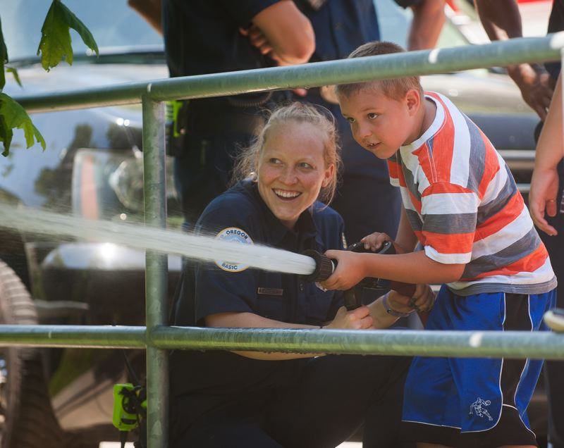 OUTLOOK PHOTO: JOSH KULLA - Gresham firefighter Emily Snodgrass enjoys a laugh with 7-year-old Chris Gonzales of Gresham Friday at Main City Park as part of the city of Gresham's Summer Kids in the Park opening week.