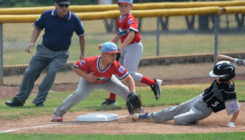 OUTLOOK PHOTO: DAVID BALL - Reynolds Dustin Hayden slides safely into third base while Centennials Evan Melton stops the ball during the first inning of the Ragers 15-5 minors win Friday.